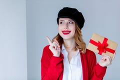 红色羊毛衫的有礼物盒的妇女和帽子 免版税库存图片