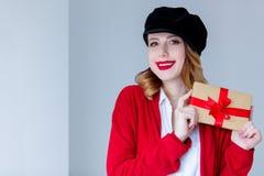红色羊毛衫的有礼物盒的妇女和帽子 免版税库存照片