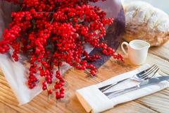 红色美洲冬青花圣诞节花束在一张木桌上的 免版税库存图片