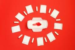 红色羽毛和月经带和吸收剂板料在红色背景 免版税库存照片