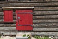 红色老门和窗口在村庄房子的木墙壁上 非常好的背景 免版税库存图片