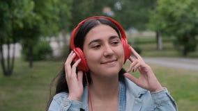 红色耳机的美女步行沿着向下街道和听到音乐的 ?? 股票视频