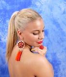 红色耳环的年轻美丽的女孩在抽象背景 库存图片