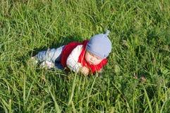 红色背心的婴孩在户外草 库存照片