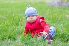 红色背心的婴孩坐草在公园 库存图片