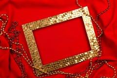 红色背景 金黄和红色小珠,相框 免版税库存照片