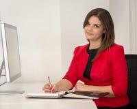 红色腰部外套文字笔记的女商人 免版税库存照片