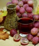 红色自然酒自创柳条瓶和葡萄 免版税库存图片