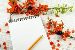红色花和一个笔记本的构成笔记的关于木 免版税库存照片