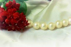 红色花和珍珠项链 免版税库存图片