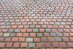 红色花岗岩铺路石的老路面 免版税库存照片