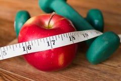 红色苹果、卷尺和哑铃 库存图片