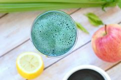 从红色苹果、绿藻类spirulina、柠檬和芹菜的健康新圆滑的人饮料在木背景的玻璃 库存图片