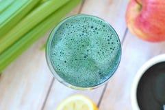 从红色苹果、绿藻类spirulina、柠檬和芹菜的健康新圆滑的人饮料在木背景的玻璃 图库摄影