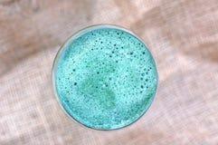 从红色苹果、绿藻类spirulina、柠檬和芹菜的健康新圆滑的人饮料在棕色背景的玻璃 免版税库存图片
