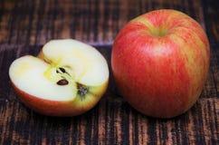 红色苹果和一个一半在桌上 免版税库存照片