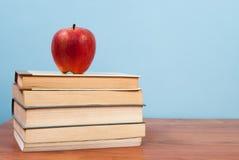红色苹果和书在一个木桌和蓝色背景和自由空间上文本的 免版税库存照片