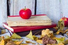红色苹果和书在白色木背景,秋天概念 库存照片