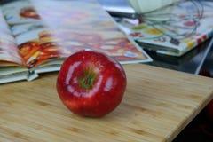 红色苹果和厨师书 免版税库存照片