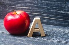 红色苹果和在A上写字 初等教育的概念 苹果计算机 免版税库存照片