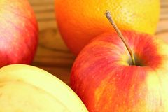 红色苹果和橙色背景的温暖的被日光照射了关闭 库存照片