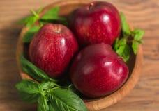 红色苹果在木盘关闭  免版税库存照片