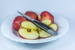 红色苹果用刀子切成了两半 库存照片