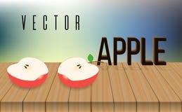 红色苹果,迷离背景两halfs在木桌上的 库存图片
