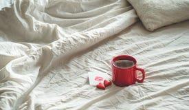 红色茶和两个心脏曲奇饼,与一个亲吻的笔记在一张白色床上 背景蓝色框概念概念性日礼品重点查出珠宝信函生活纤管红色仍然被塑造的华伦泰 库存照片