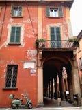 红色茶黄门面和停放的摩托车,波隆纳,意大利 库存图片