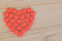 红色药片在形状心脏 库存照片