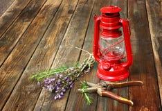 红色葡萄酒煤油灯和贤哲花在木桌。艺术概念。 免版税库存图片