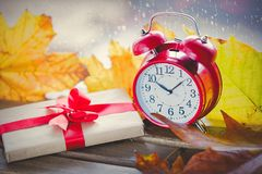红色葡萄酒闹钟和礼物盒有槭树的离开 库存照片