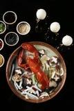 红色蒸了龙虾用在板材的蘑菇在黑背景 免版税图库摄影
