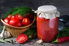 红色蕃茄和新鲜的西红柿酱用莳萝,大蒜,胡椒在一张木桌上 免版税库存图片