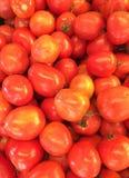 红色蕃茄在义卖市场一起堆了 免版税库存照片