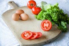 红色蕃茄,莴苣,鸡蛋,在老木背景 准备的一顿素食早餐过程 免版税库存图片