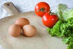 红色蕃茄,莴苣,鸡蛋,在老木背景 准备的一顿素食早餐过程 库存图片