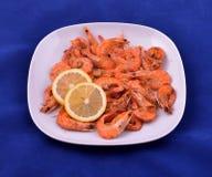 红色虾烹调用黄油、大蒜和柠檬在白色板材 库存图片