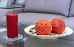 红色蜡烛和一块板材有两个橙色球的 免版税库存照片
