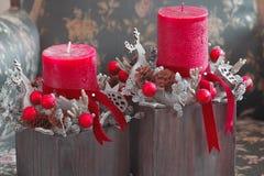 红色蜡烛和木圣诞老人鹿在圣诞节制表装饰 库存照片