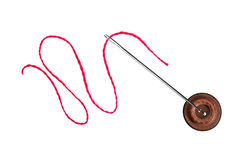 红色螺纹、在白色隔绝的针和按钮 库存照片