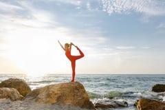红色衣服实践的瑜伽的一名妇女在日出的石头在海附近 免版税图库摄影