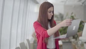 红色衣服的年轻女人键入在她的小配件的在现代轻的办公室 女孩结束她的netbook和微笑 E 影视素材