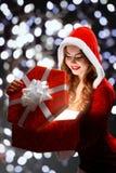 红色衣服的微笑雪的未婚拿着礼物,打开礼物  免版税图库摄影