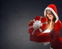 红色衣服的微笑雪的未婚拿着礼物,打开礼物  免版税库存图片