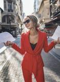 红色衣服的笑的时髦的女人拿着纸 免版税库存照片
