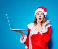 红色衣裳的圣诞老人Clous女孩有便携式计算机的 库存照片