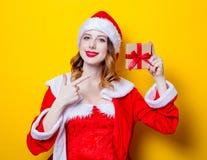 红色衣裳的圣诞老人Clous女孩有礼物盒的 免版税图库摄影