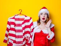 红色衣裳的圣诞老人Clous女孩有衬衣的 免版税库存照片